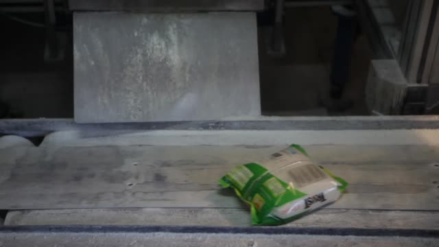 One kilogram sugar packets move along conveyor belt in the packaging unit of the Simbhaoli Sugars Ltd mill in Ghaziabad Uttar Pradesh A worker weighs...
