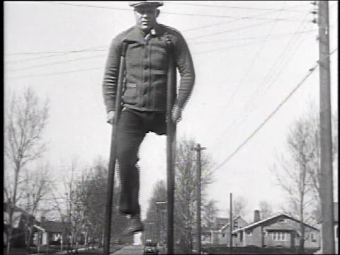 1930 ws one legged man using very tall crutches / galeseburg, illinois, usa - disability services stock videos & royalty-free footage