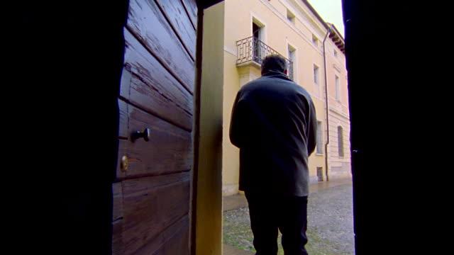 ms ts one man going from in door with holding umbrella and walking ahead / bonferraro di sorga, verona, italy - ombrello video stock e b–roll