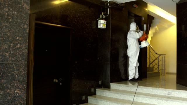 one man in protective suit disinfecting the apartment entry - cleaner stock videos & royalty-free footage