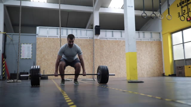 one man lifting heavy weights in gym - cross training stock videos & royalty-free footage