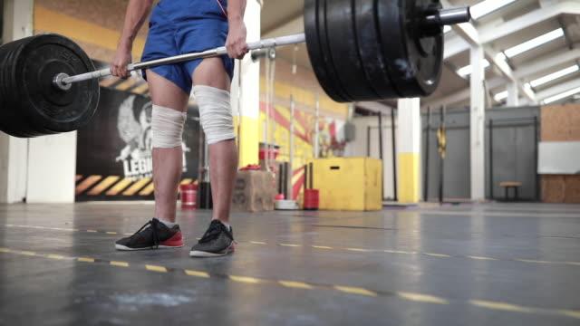 一人の男がジムで重い重量を持ち上げる - 重い点の映像素材/bロール