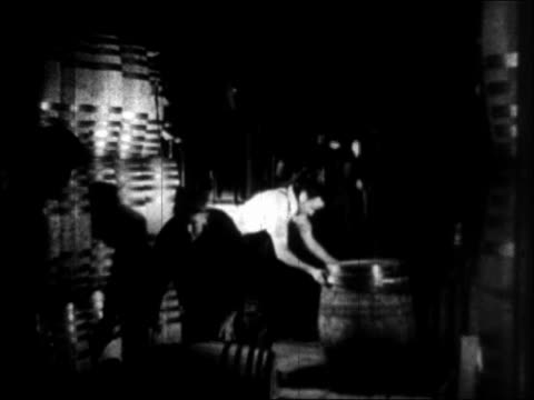 b/w 1933 one man putting rings on barrel of beer second man rolling barrel in brewery - anno 1933 video stock e b–roll