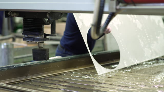 One man removing a sheet of metal from a water jet cutter