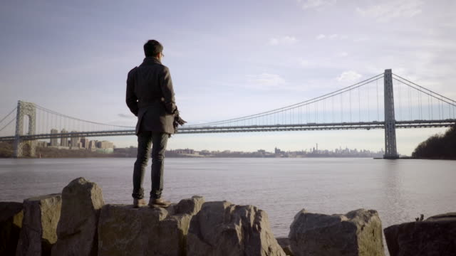 one man standing alone at river pier looking at bridge