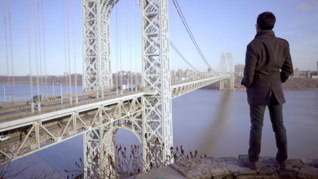 one man standing on top of hill overlooking river bridge