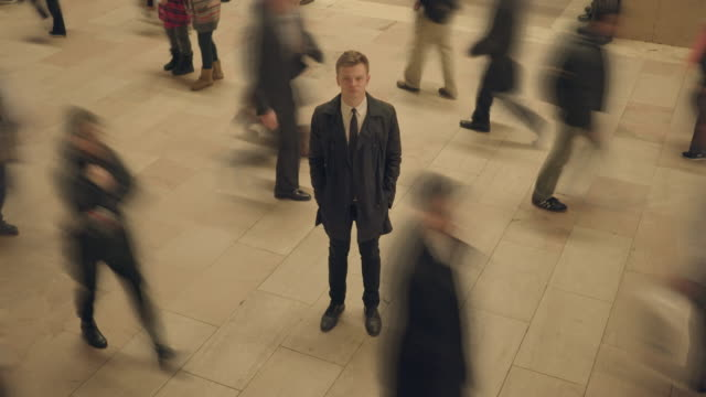 vidéos et rushes de one man standing out of the crowd. young caucasian businessman surrounded by walking people - une seule personne