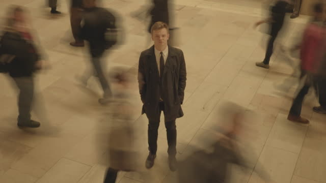 vidéos et rushes de one man standing out of the crowd. young caucasian businessman surrounded by walking people - individualité