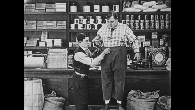 vídeos y material grabado en eventos de stock de 1919 one man (buster keaton) takes another man's (fatty arbuckle) measurements - cinta métrica