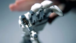 One man touches a prosthetic hand, close up.