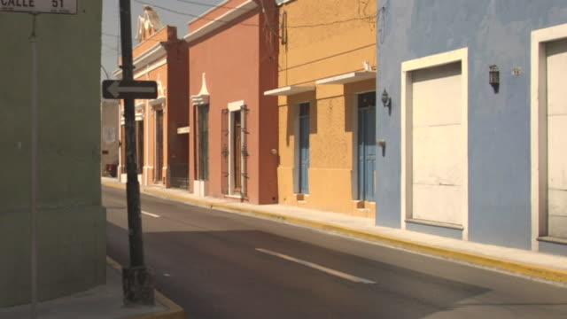 vídeos y material grabado en eventos de stock de ws pan one man walking down empty street / merida, mexico  - mérida méxico