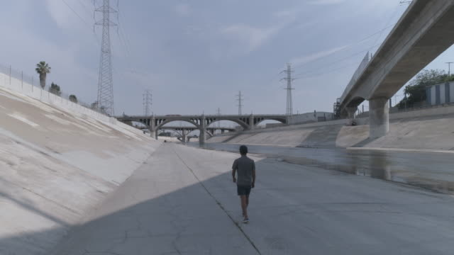 one man walking in the la river - concrete stock videos & royalty-free footage