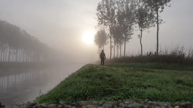one man wearing mask doing some outdoor workout during covid period near a river in a foggy morning - pjphoto69 stock videos & royalty-free footage