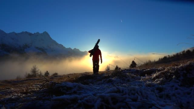 One man with ski walking at sunset on the snowed mountian