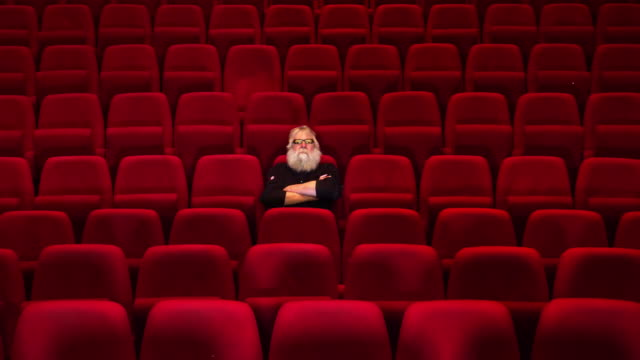 one man with white beard sits in empty cinema or theatre with , enters - chair stock videos & royalty-free footage