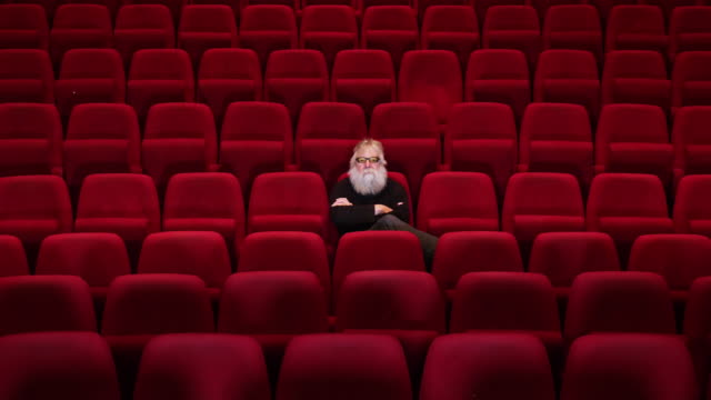 One man with white beard sits in Empty cinema or theatre with , leaving