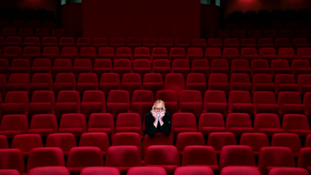 one man with white beard sits in empty cinema or theatre with , leaving - cinema stock videos & royalty-free footage
