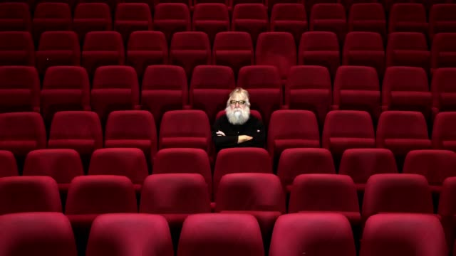 one man with white beard sits in empty cinema or theatre with comfortable red seats, leaving - disappointment stock videos and b-roll footage