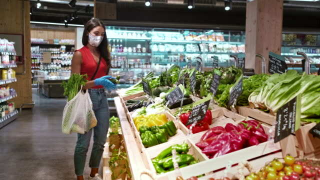 vídeos de stock e filmes b-roll de one millenial costumer choosing vegetables and wearing a protective mask. - environmental issues