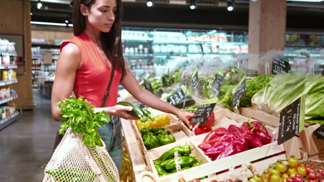 one millenial costumer choosing vegetables in a small business - reusable bag stock videos & royalty-free footage
