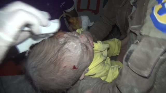 one month old baby boy is being taken to hospital by civil defence members after he was pulled out from the wreckage of a building hit by assad... - air raid点の映像素材/bロール