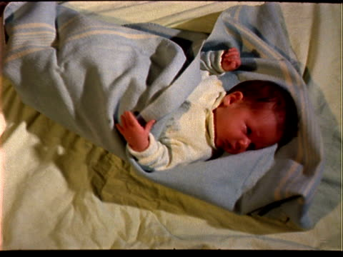 one month old infant baby wearing fuzzy light yellow jumper, squirming in baby blue blankets. one month old baby on january 01, 1958 - 1958年点の映像素材/bロール
