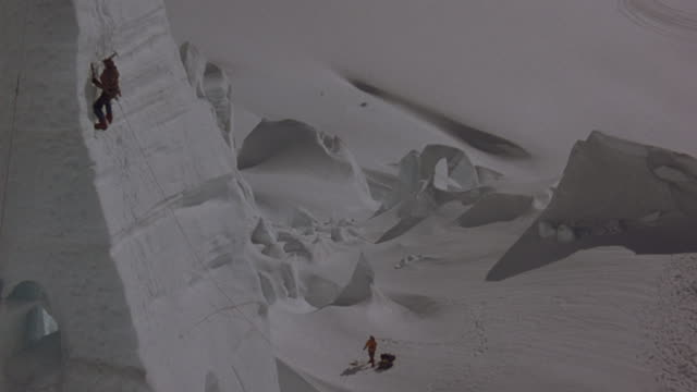 one mountain climber scales a steep snowy face while another stands far below. - icepick stock videos and b-roll footage
