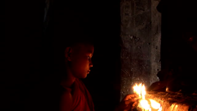 One novice monk lighting candles with Buddha HDV165