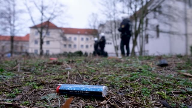 one of dozens of cigarette lighters thrown in protest by activists lies on the ground outside the offices of the state prosecutor as riot police walk... - feuerzeug stock-videos und b-roll-filmmaterial