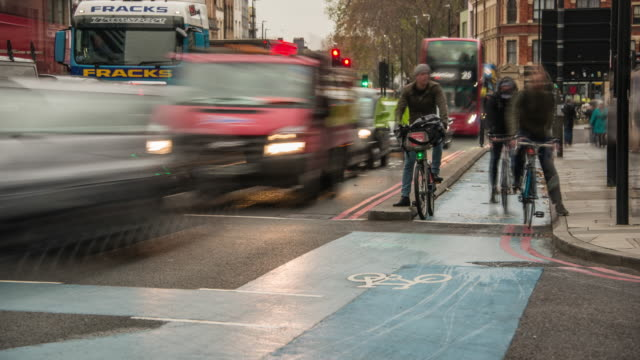 vídeos de stock e filmes b-roll de one of london's new cycle superhighways helps to improve the safety of cyclists during the morning rush hour into the city - road junction