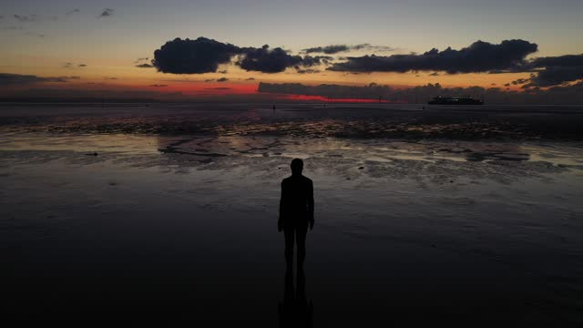 one of the 100 life-size body cast statues of 'another place' created by the artist sir antony gormley looks out over the mersey estuary at sunset on... - coastal feature stock videos & royalty-free footage