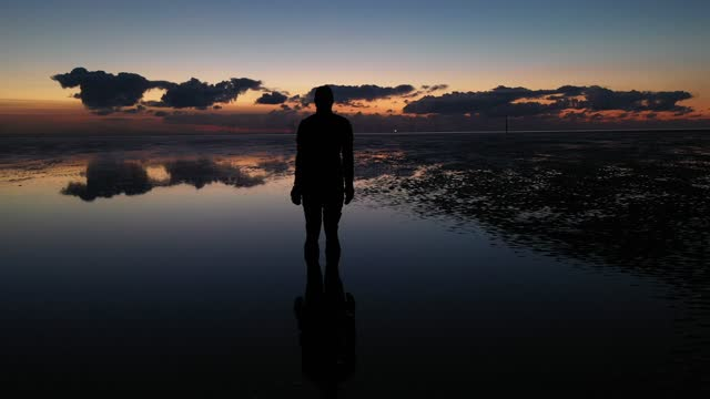 one of the 100 life-size body cast statues of 'another place' created by the artist sir antony gormley looks out over the mersey estuary at sunset on... - scenics stock videos & royalty-free footage