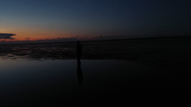 one of the 100 life-size body cast statues of 'another place' created by the artist sir antony gormley looks out over the mersey estuary at sunset on... - sculpture stock videos & royalty-free footage