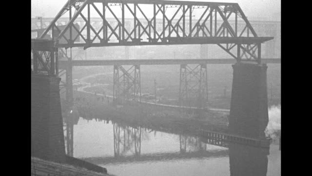 one of the bridge's pylons with men drilling into it and a damaged portion of the wall / a wideshot view of the structure with explosions at lower... - fiume cuyahoga video stock e b–roll
