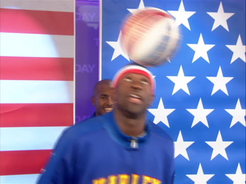 one of the harlem globetrotters spins a basketball on his head the harlem globetrotters are an exhibition basketball team that combines athleticism... - roy e. disney stock videos & royalty-free footage