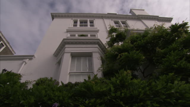 vídeos de stock, filmes e b-roll de one of the many mansion flats in little venice is surrounded by lush trees. available in hd. - janela saliente