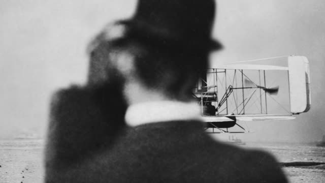 One of the Wright Brothers photographs the test flight of a biplane.
