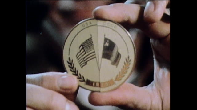 one person shows a medal with the flags of the usa and the former ussr the date is circa 1976 elements of this image furnished by nasa - mir space station stock-videos und b-roll-filmmaterial