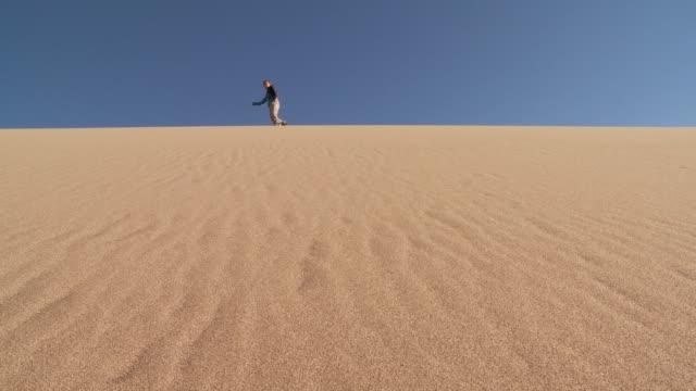 WS POV One person standing on sand dome ridge then skiing down on dune / San Pedro de Atacama, Norte Grande, Chile