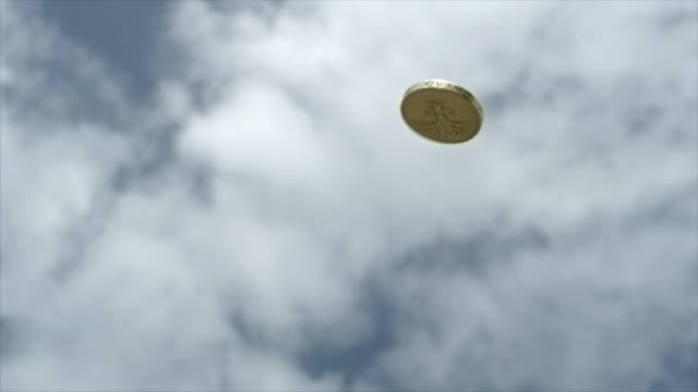 A one pound coin spinning in the air against a blue sky with white clouds