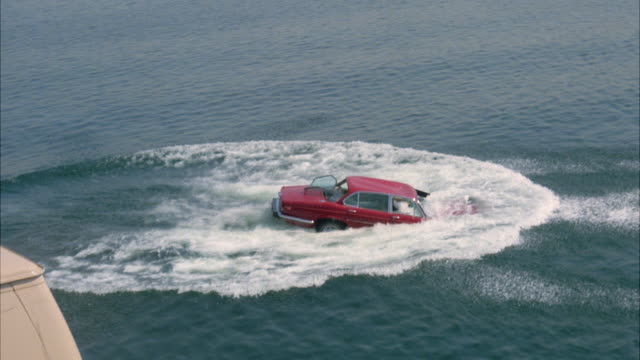vidéos et rushes de ms pan one red car jumping in water - exploit sportif