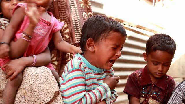 ein ländliches indischen jungen weinen inmitten der gruppe von kindern - geschwister stock-videos und b-roll-filmmaterial