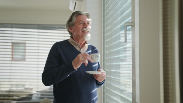 one senior caucasian man drinking coffee and standing next to a window - blinds stock videos & royalty-free footage
