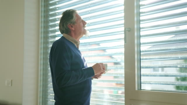 vídeos de stock e filmes b-roll de one senior caucasian man drinking coffee and standing next to a window - domingo