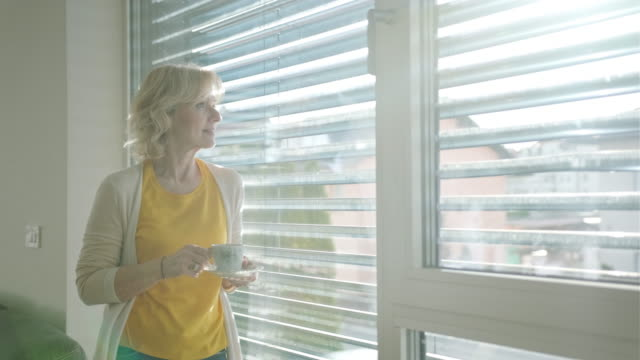 one senior caucasian woman drinking coffee and standing next to a window - blinds stock videos & royalty-free footage