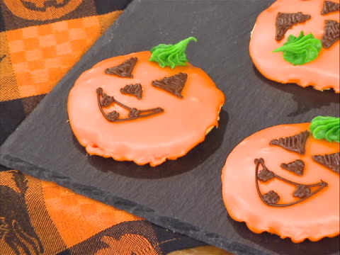 one shot it starts off with a close up of pumpkin shaped cookies on a table with halloween tablecloth underneath with little pumpkin designs on it.... - tablecloth stock videos & royalty-free footage