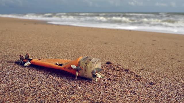 風の強いビーチでプラスチック製の日焼けローションボトル汚染を1回使用 - ムール貝点の映像素材/bロール