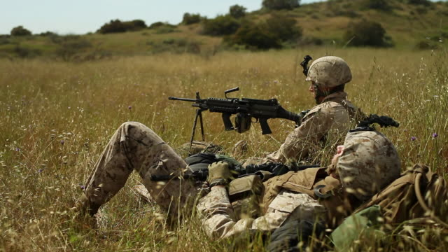 MS One soldier slepeping on grass another soldier with heavy machine gun keeping watch AUDIO / Camp Pendleton, CA, United States