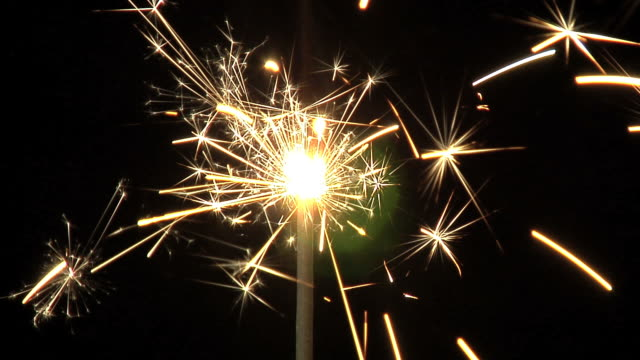 One sparkler in darkness with lens flare