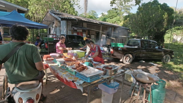 one thai man buying fried chicken from outdoor street food vendor - agricultural fair stock videos & royalty-free footage